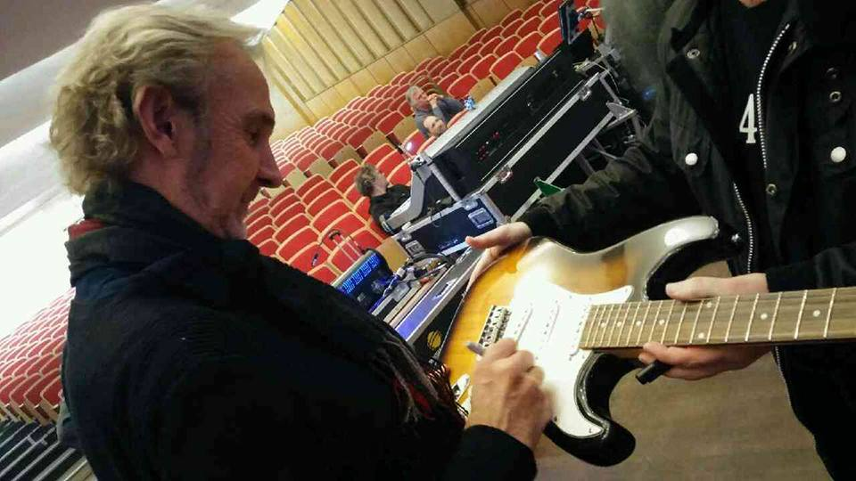 Mike Rutherford signing the guitar at the Colston Hall (Pic: HorseWorld)