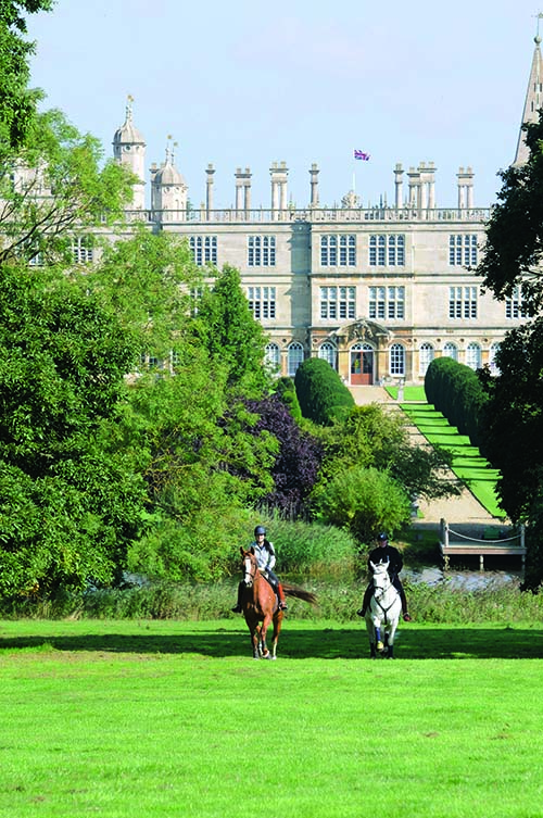 Riding horses in front of Burghlye House