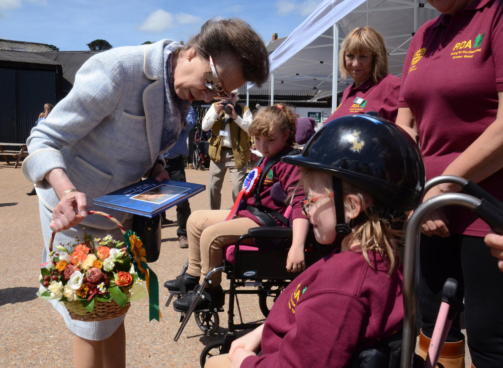 Rider Sophie Case presenting HRH The Princess Royal with a posy
