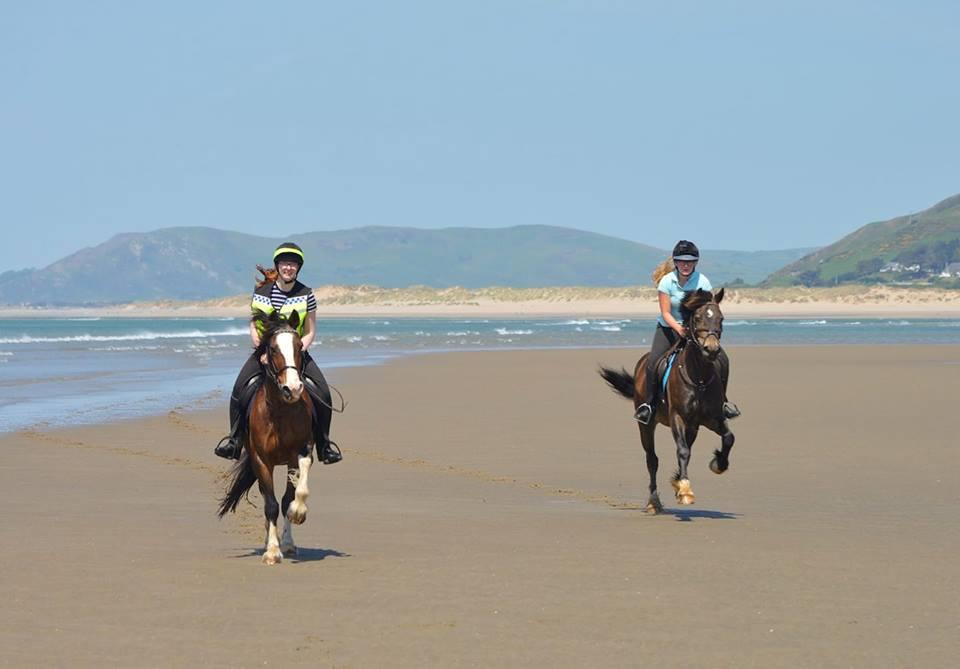 Eleanor Laws and friend enjoy a beach ride