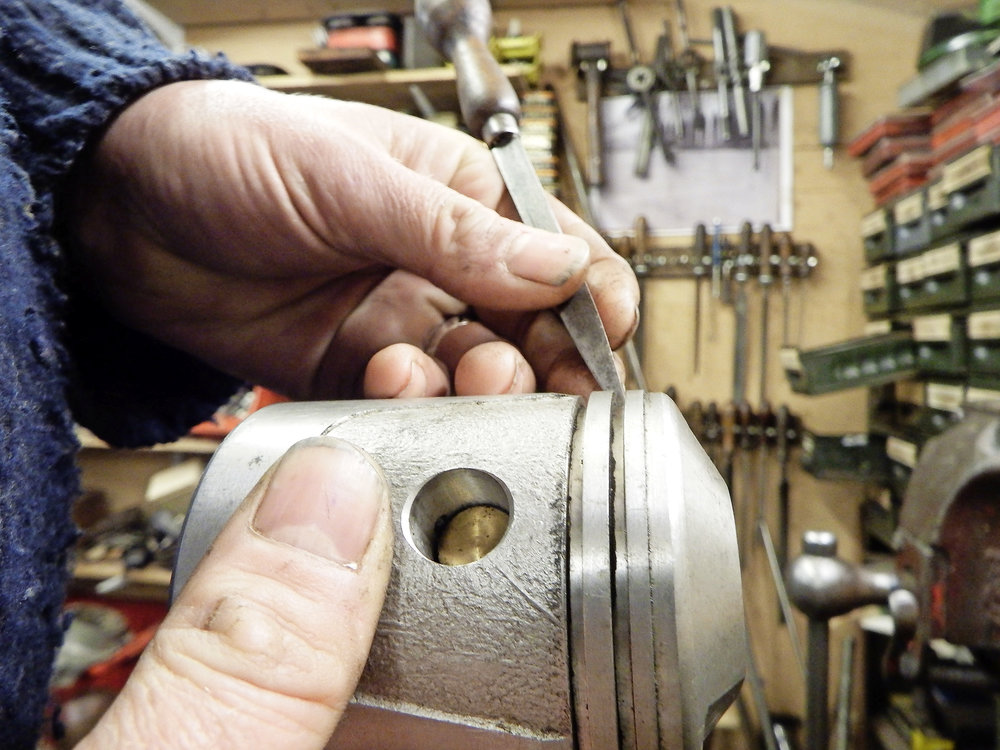 Gently relieving the edge of a piston ring groove removes burrs