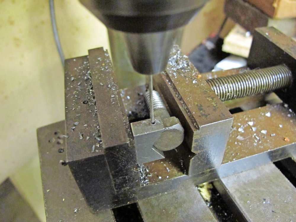 4. With the bolt-head located into the jig and clamped into a machine vice, the drilled hole guides the fine bit neatly through the corner of the hexagon without skidding.