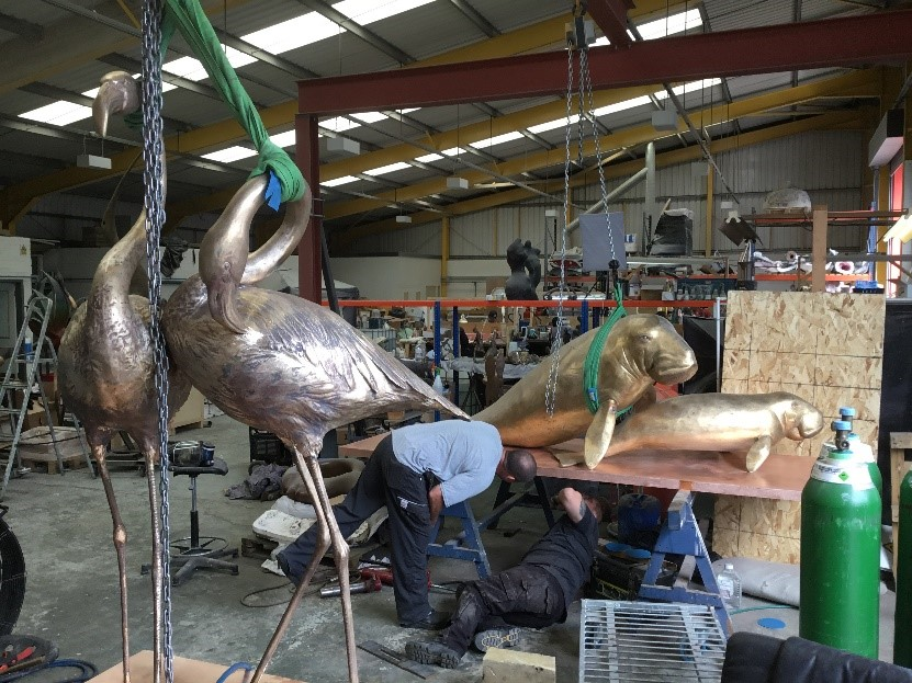 Chasers working on the Dugong base, Flamingos awaiting patination in the foreground