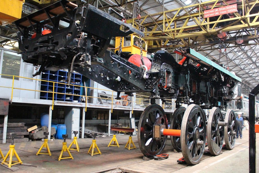 The frames of 'Merchant Navy' No. 35005  Canadian Pacific  are carefully lowered onto the driving wheels inside Eastleigh works on September 26. MHR/CANPAC
