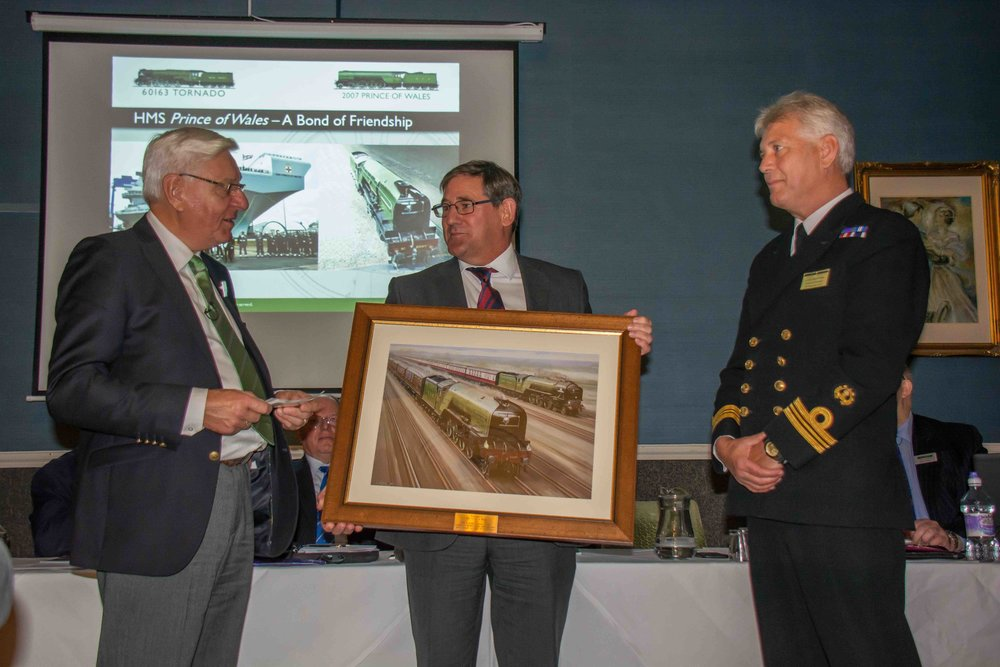 Forging a 'bond of friendship', the A1SLT hands over the painting 'Dream Team' – depicting both 'A1' No. 601063  Tornado  and 'P2' No. 2007  Prince of Wales  – to Lt Cdr David Wright. MANDY GRANT