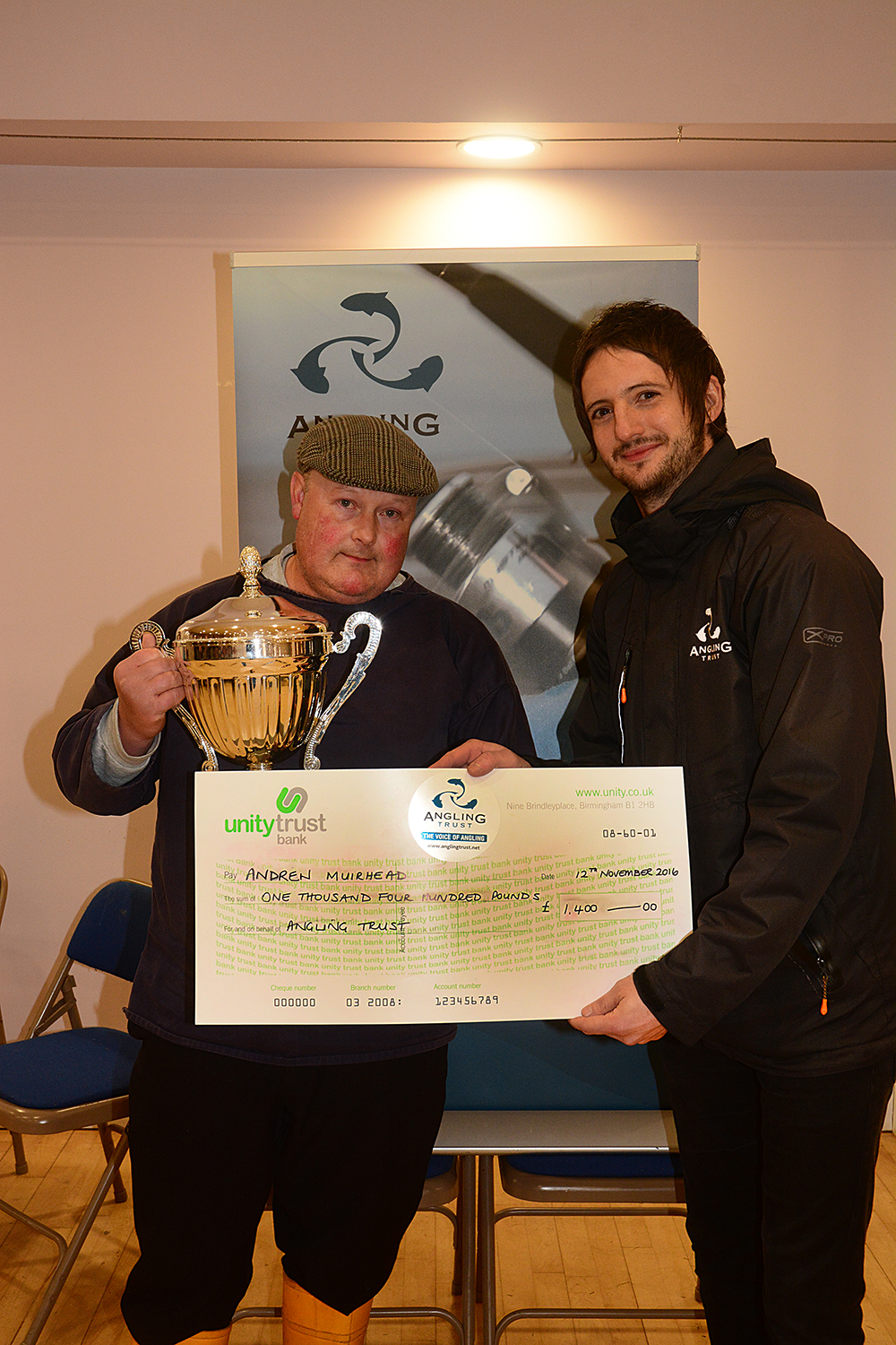 The Angling Trust's James Roche presents Andrew Muirhead with his cheque.