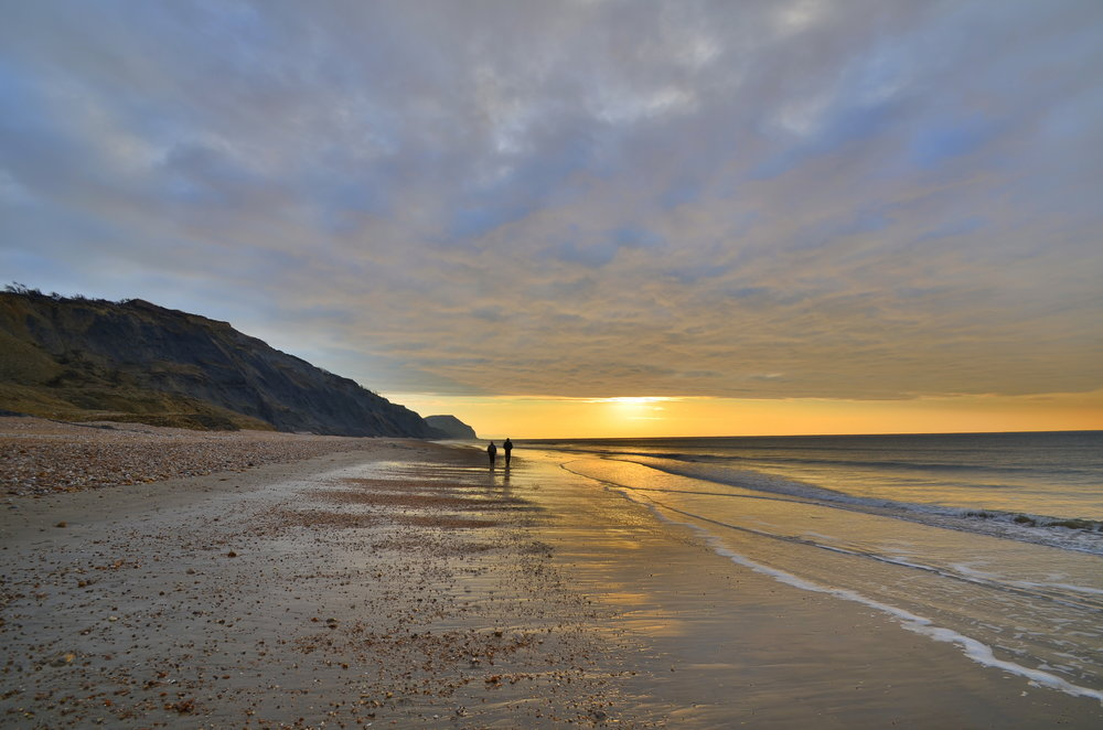 Strolling along Charmouth Beach in search of fossills.