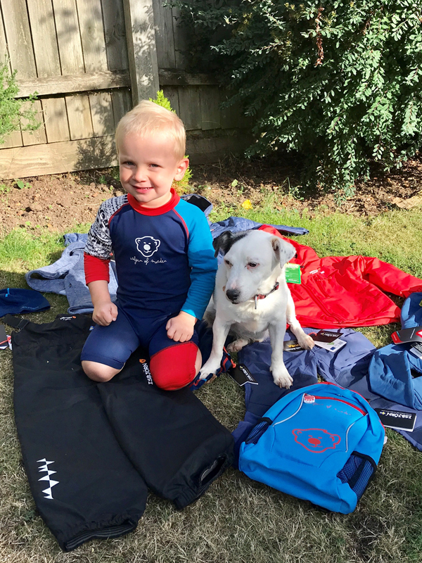 two year old Isbjorn brand ambassador Sonny Reed with dog Mario surrounded by some of  the Isbjorn products he will be wearing in the outdoors.jpg