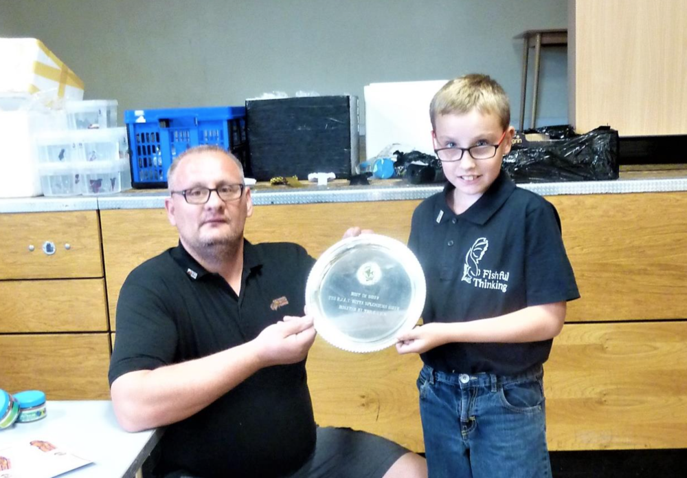 The Betta Society's Jamie Horne presents Harvey Claydon-Baldwin with the plaque for Best in Show.
