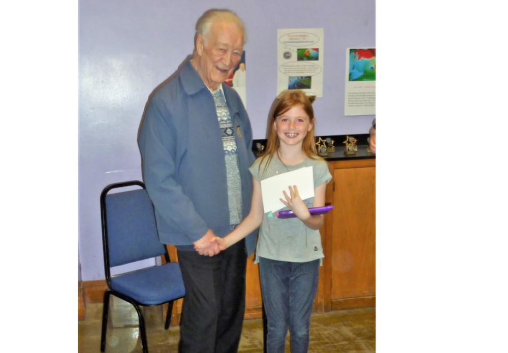 The 90-year-old President of the Northern Goldfish & Pondkeepers Society, Bill Ramsden, congratulates seven-year-old junior member Millie Clinton on a First win at their annual Open Show.