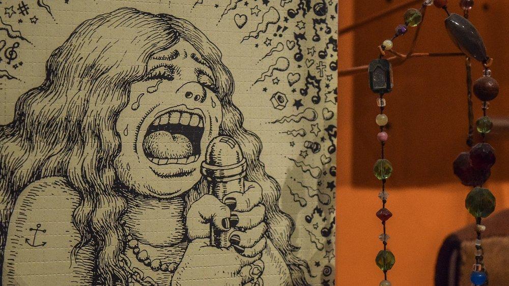 Undipped LSD blotter paper and Janis Joplin necklace.