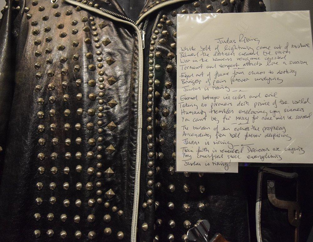 "Metal Gods. Rob Halford jacket and handwritten lyrics to ""Judas Rising""."