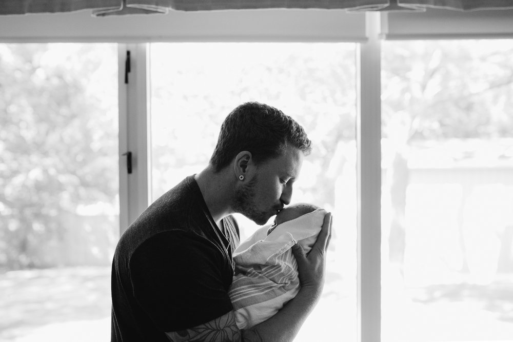 new father holding 1 day old swaddled baby girl kissing her forehead in front of window - Markham in-hospital photography