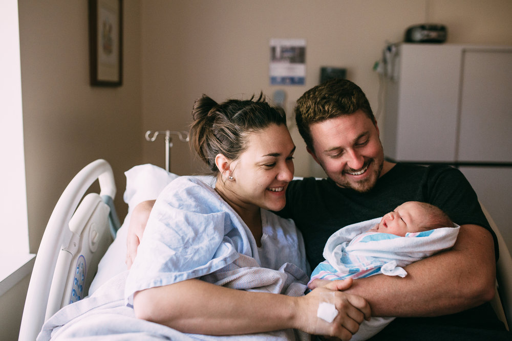 new family of 3 snuggled in hospital bed dad holding swaddled 1 day old baby girl and both parents smiling - Stouffville fresh 48 photography