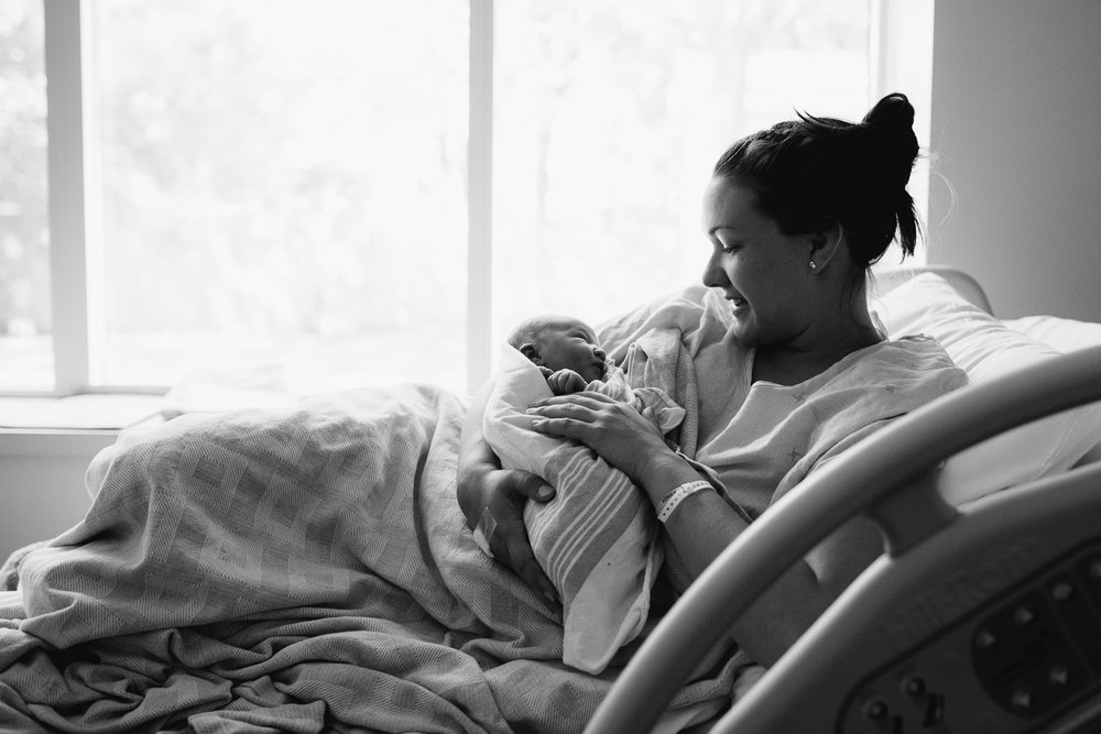 new mother sitting in hospital bed holding 1 day old baby girl swaddled and asleep - Uxbridge fresh 48 photography