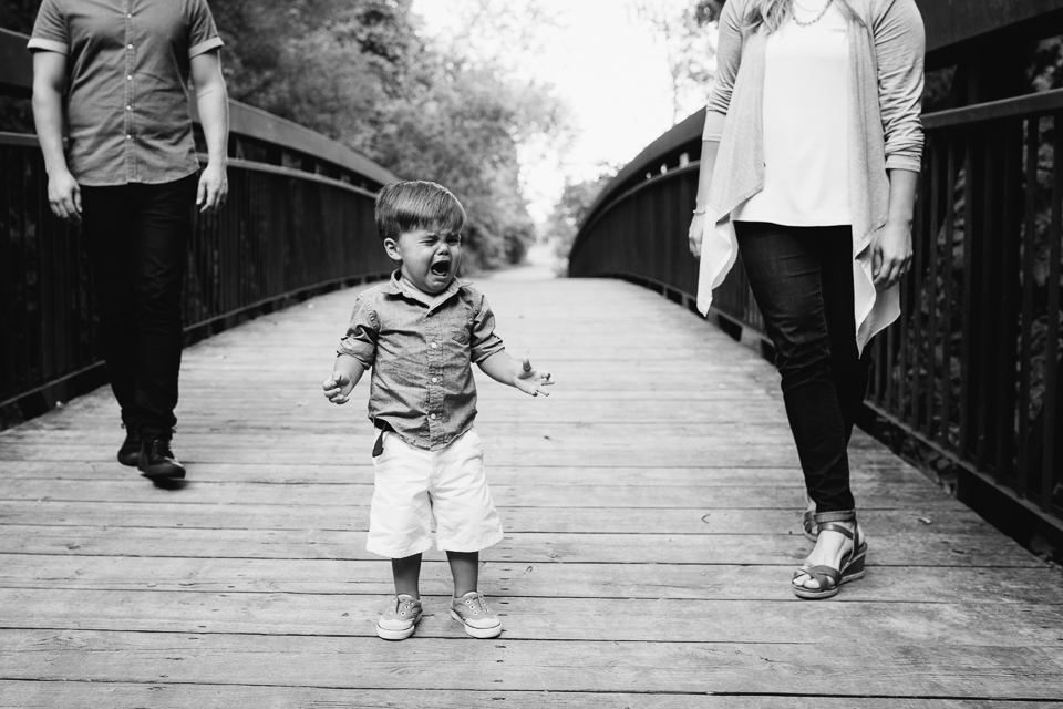 family of 3 standing on bridge while 2 year old toddler boy is crying - Newmarket child photos