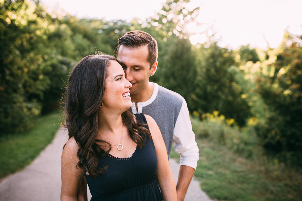 couple standing on park path wife smiling as husband whispers into ear - Newmarket lifestyle photos