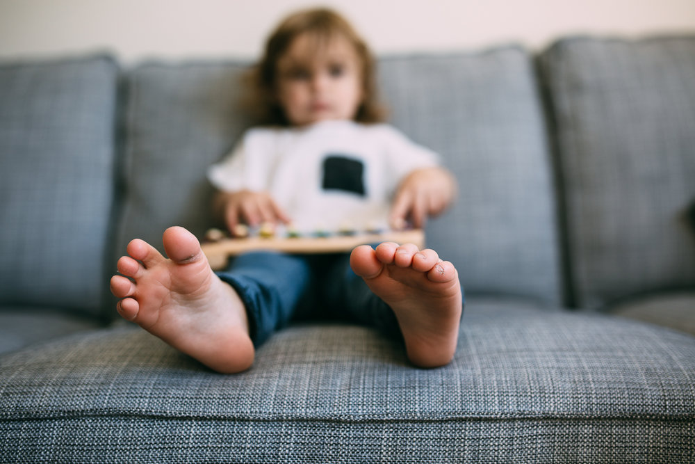 3 year old toddler boy sitting on couch playing on toy xylophone with feet sticking out - newmarket child photography