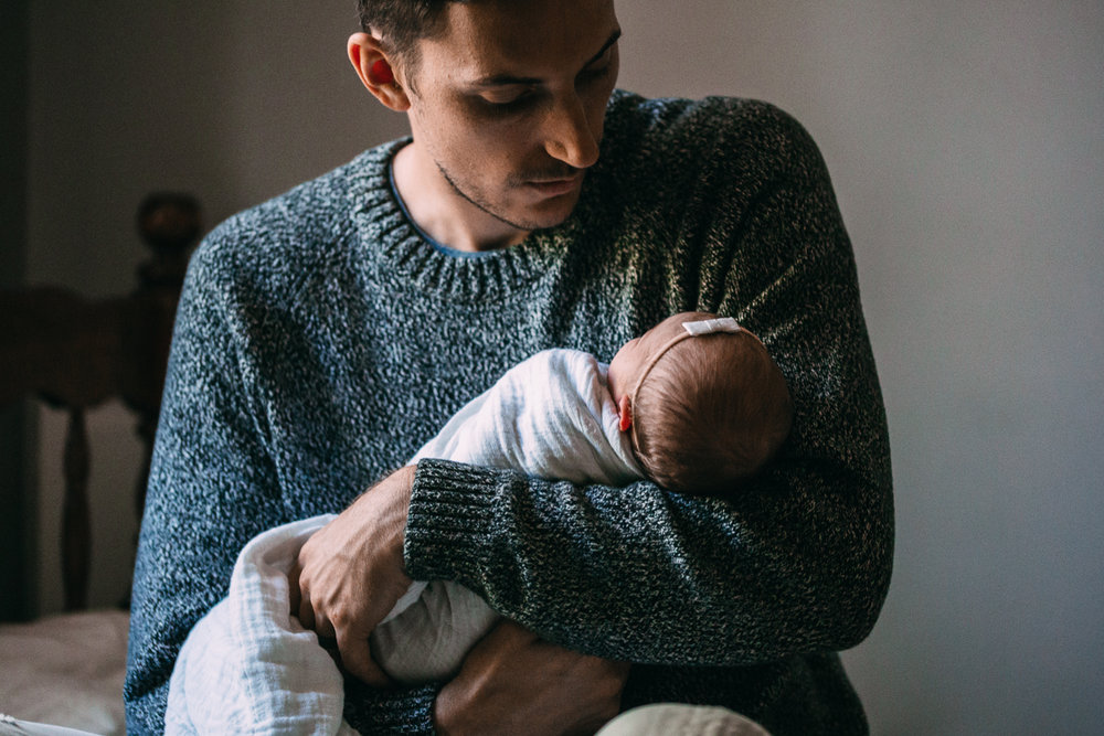 dad holding and looking at 1 week old baby daughter - Markham lifestyle photography