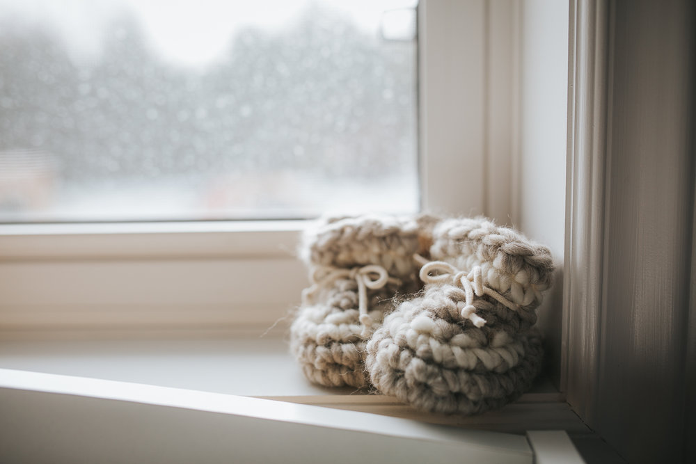 hand knit neutral cream baby booties on windowsill - newmarket newborn photography