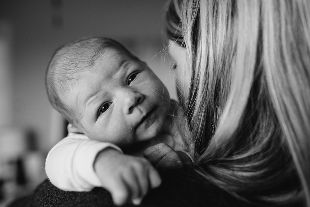 one week old baby girl looking at camera over mother's shoulder - stouffville newborn photography