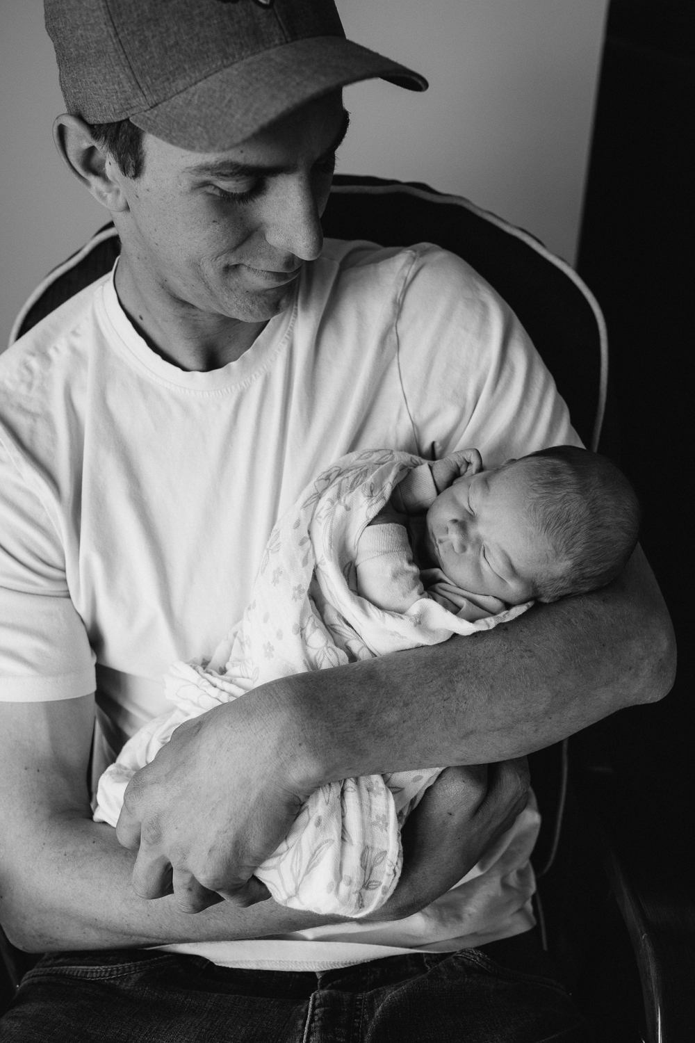 new father holding sleeping 1 week old baby girl in rocking chair - newmarket family photos