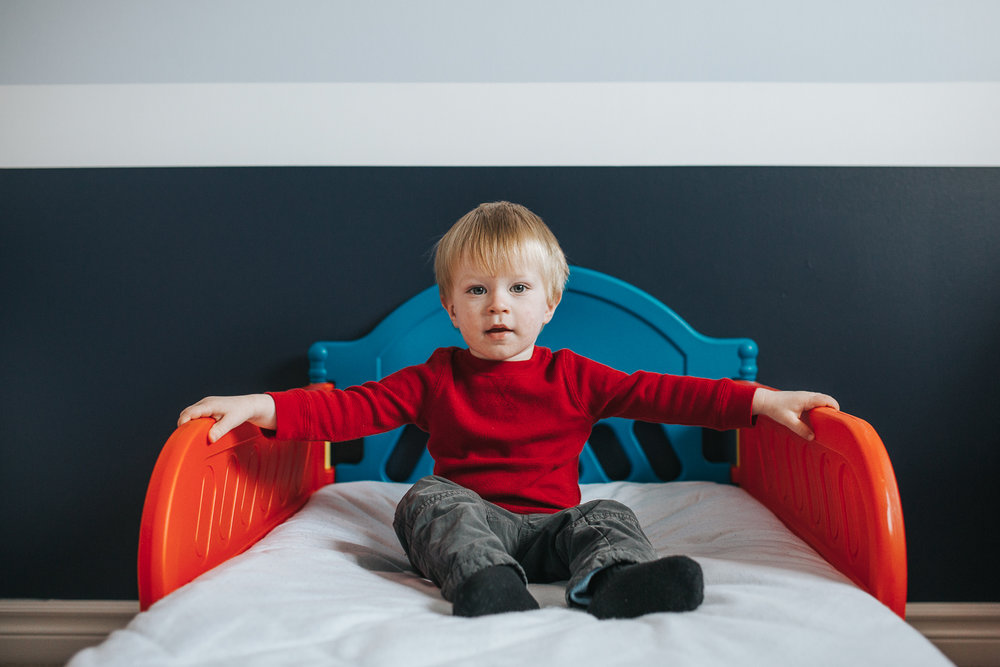 2 year old toddler boy sitting in red and blue bed looking at camera - toronto family photographer