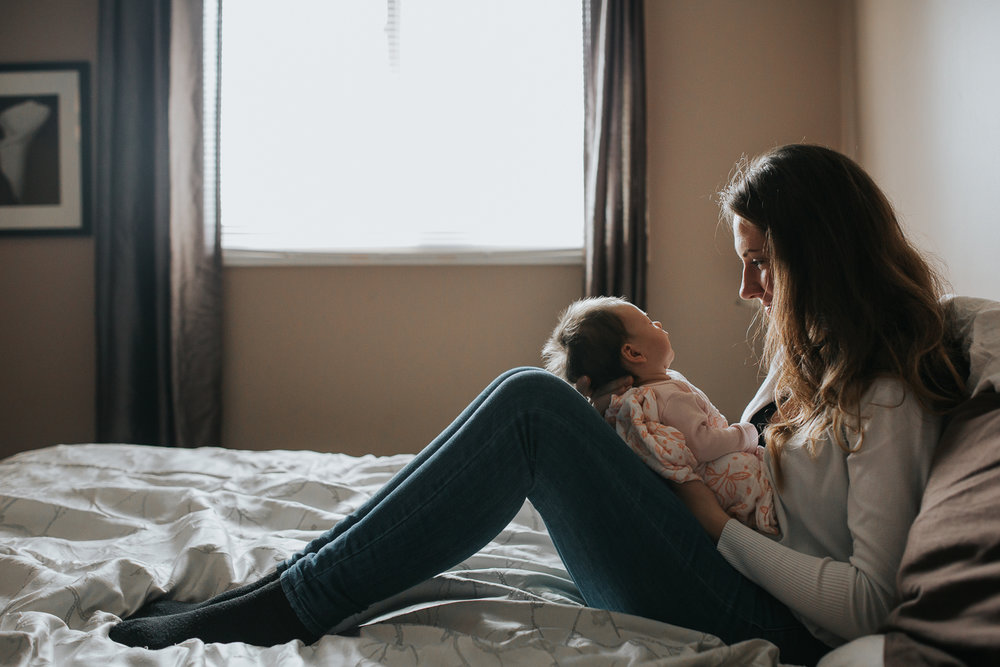 new mother with long brunette hair sitting on bed holding and looking at 1 month old baby girl - Markham newborn photography