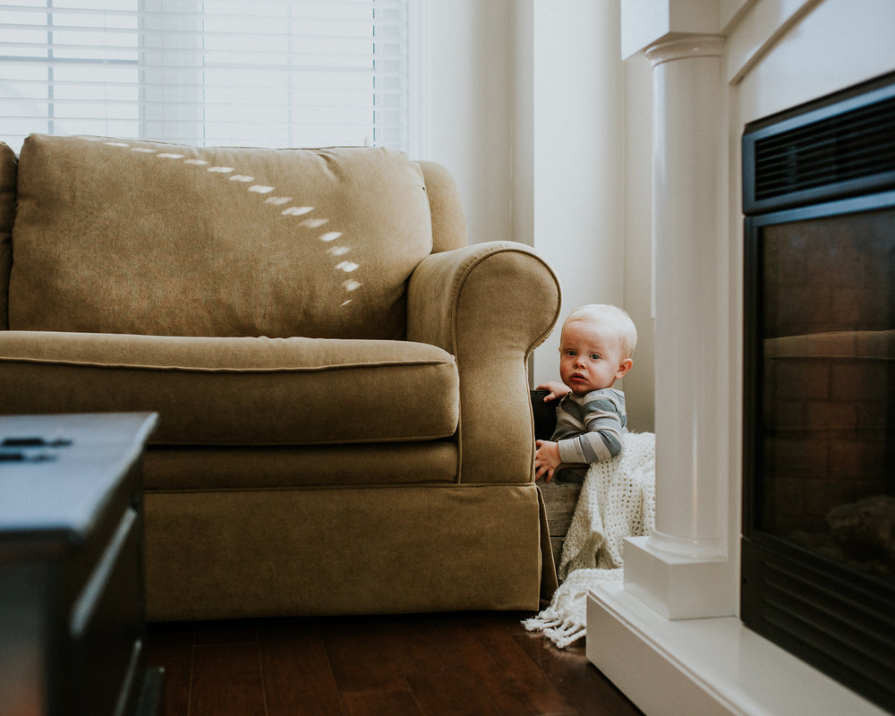 1 year old baby boy sitting in wooden box beside couch - Stouffville child photography