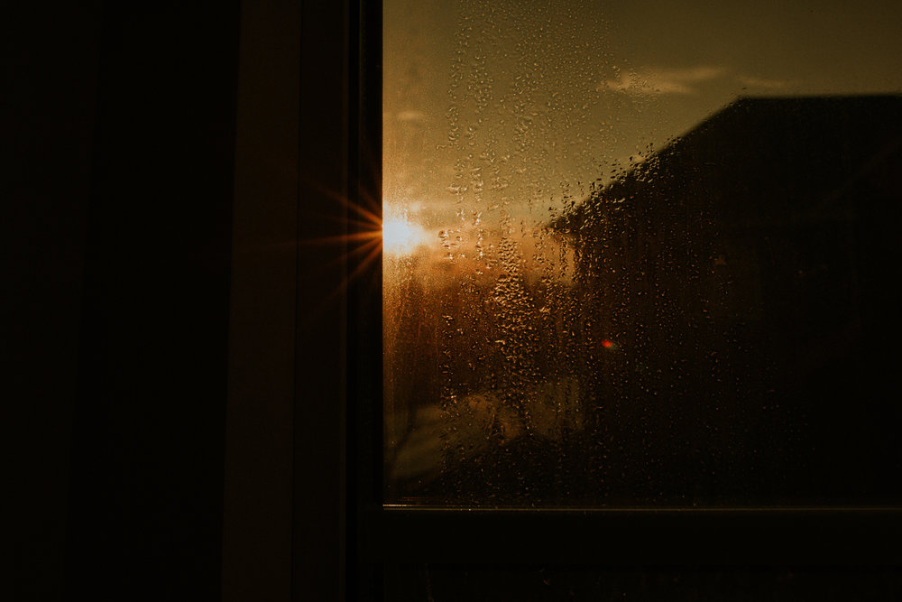 moody sunset behind house through dew drops on window - Newmarket in-home photography
