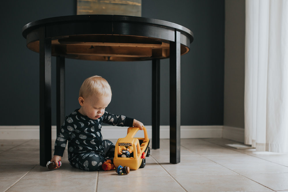 1 year old baby boy playing with little tikes yellow school bus under table in pyjamas - Uxbridge child photography