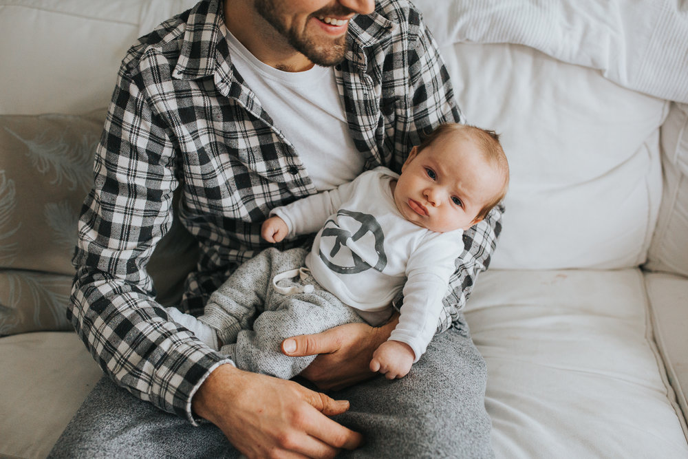 Dad holding 2 month old baby boy on couch {Toronto Family Photographer}