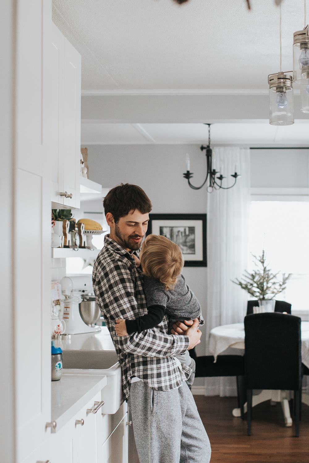 Dad holding 2 year old toddler boy in kitchen {Toronto Family Photographer}