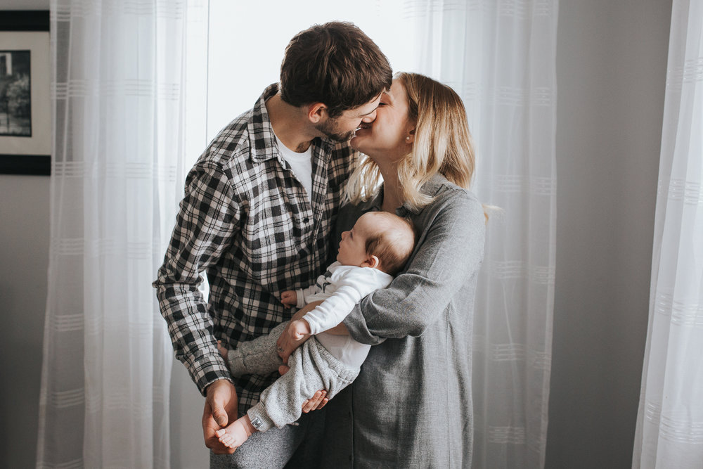 husband and wife kissing holding baby {Toronto Family Photographer}