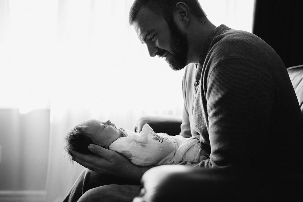 father holding and looking at 1 month old baby girl - Newmarket baby photography