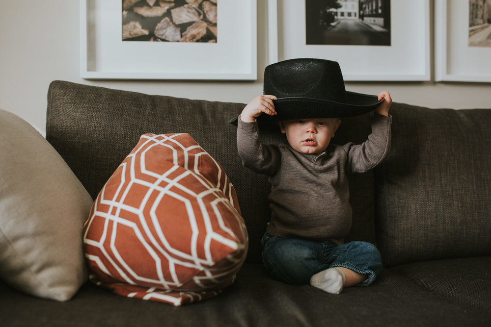 1 year old toddler boy putting on cowboy hat - markham child photography