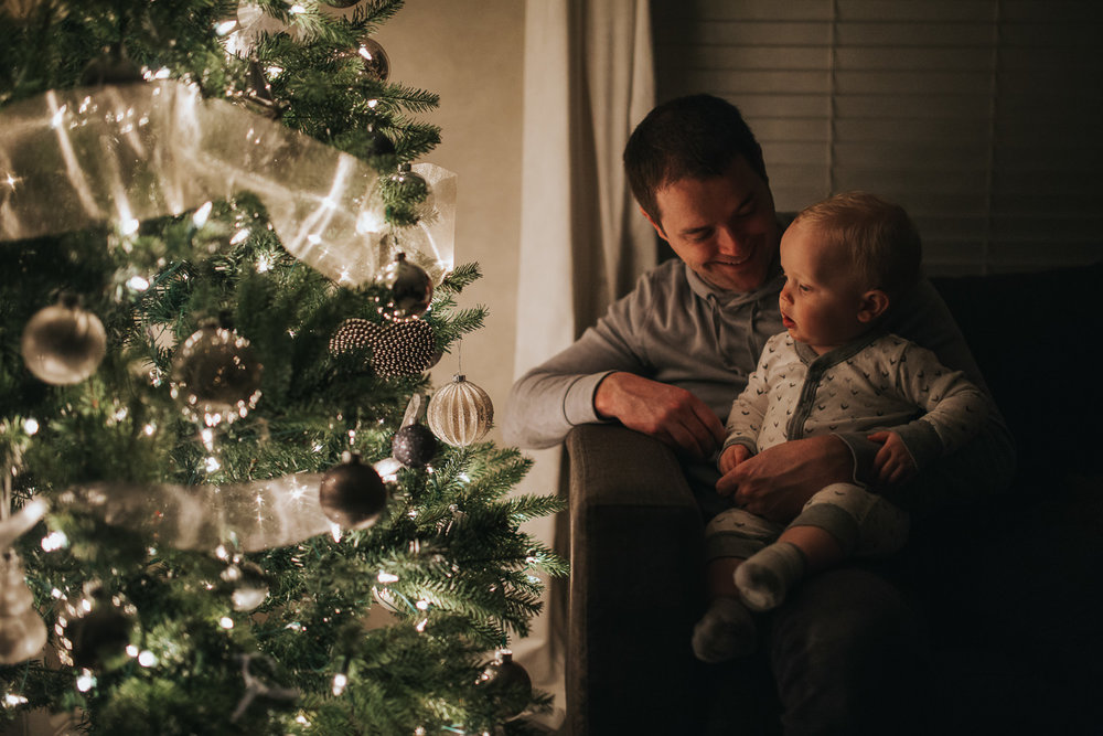 1 year old toddler boy with dad looking at christmas tree - Stouffville in-home photography