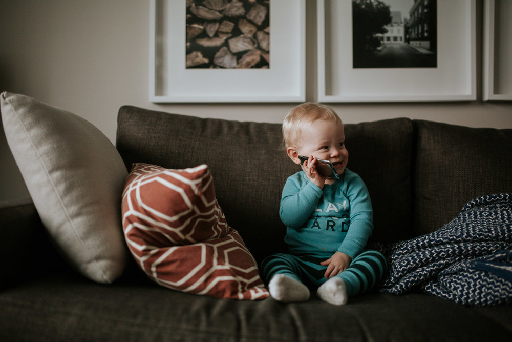 1 year old baby boy on couch talking on phone - stouffville lifestyle photography