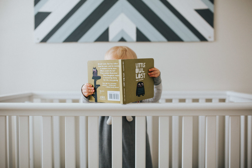 1 year old baby boy reading book in crib - Markham lifestyle photography