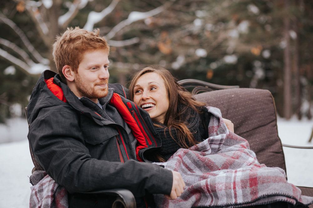 newly engaged couple sitting by fire outside in winter - newmarket lifestyle photos