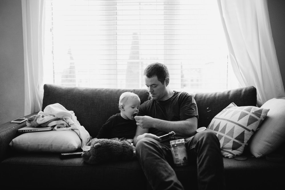 1 year old baby boy eating peanut butter on couch with father - newmarket lifestyle photography