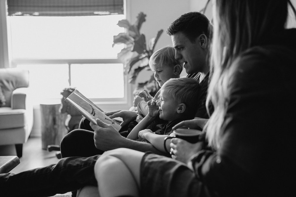 family of four with 2 blonde boys reading book on couch - Markham lifestyle photography