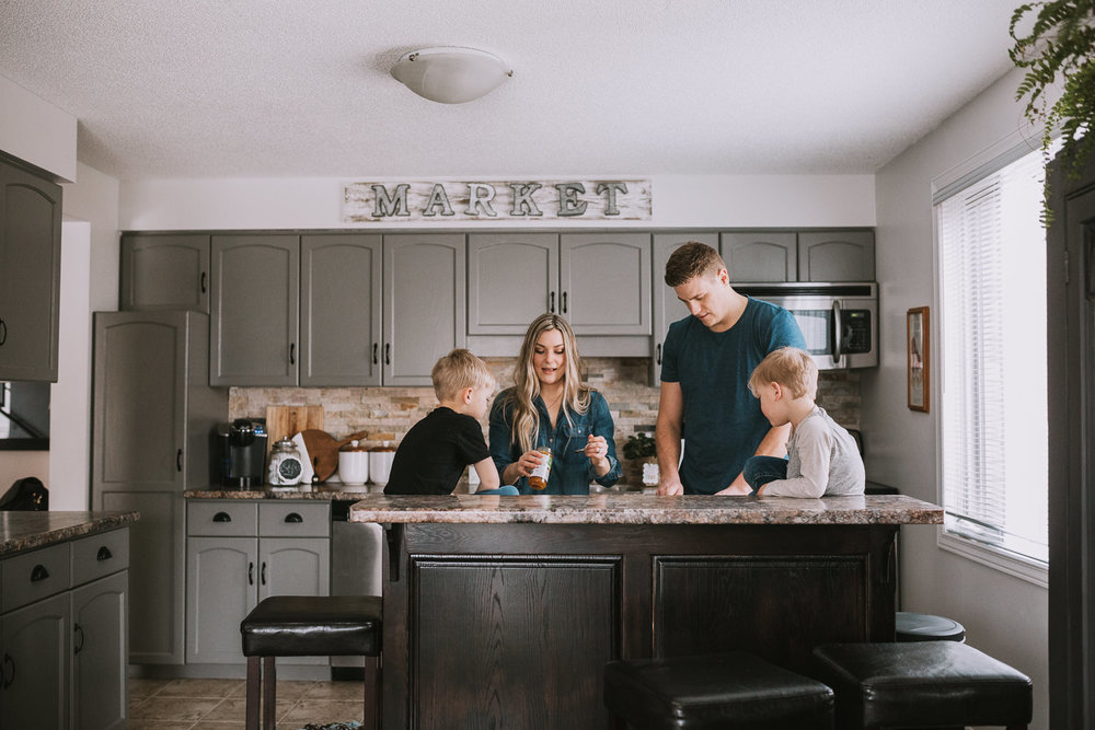 family of four with 2 young blonde boys preparing meal in kitchen - Markham lifestyle photography