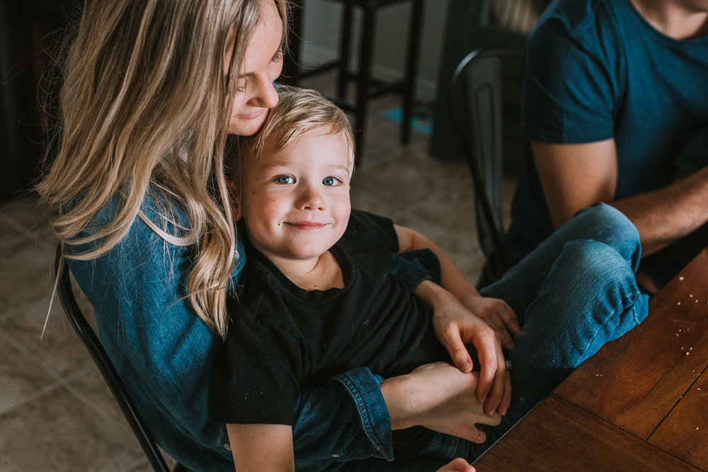 5 year old blonde boy with blue eyes looks at camera while sitting in mother's lap - Stouffville child photos