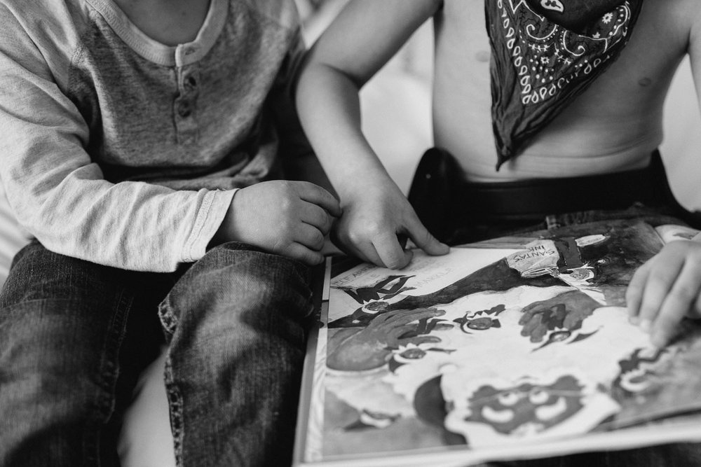 young brothers reading story together touching hands - Markham child photography