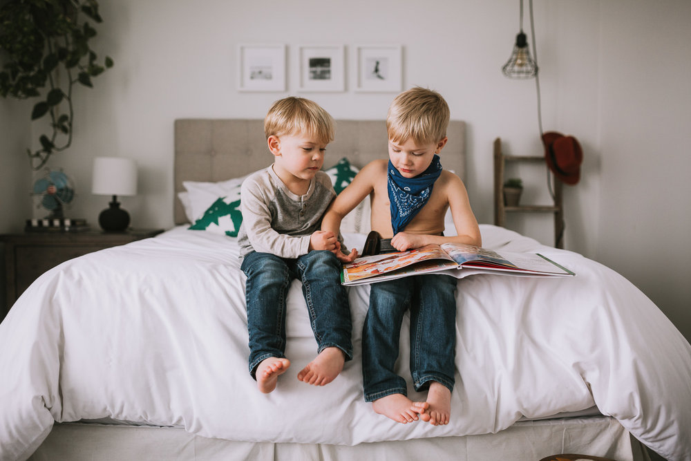 young blonde brothers reading story together on parents bed - Uxbridge child photography