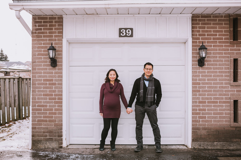 couple expecting first baby holding hands standing on front of garage door - Uxbridge lifestyle photography