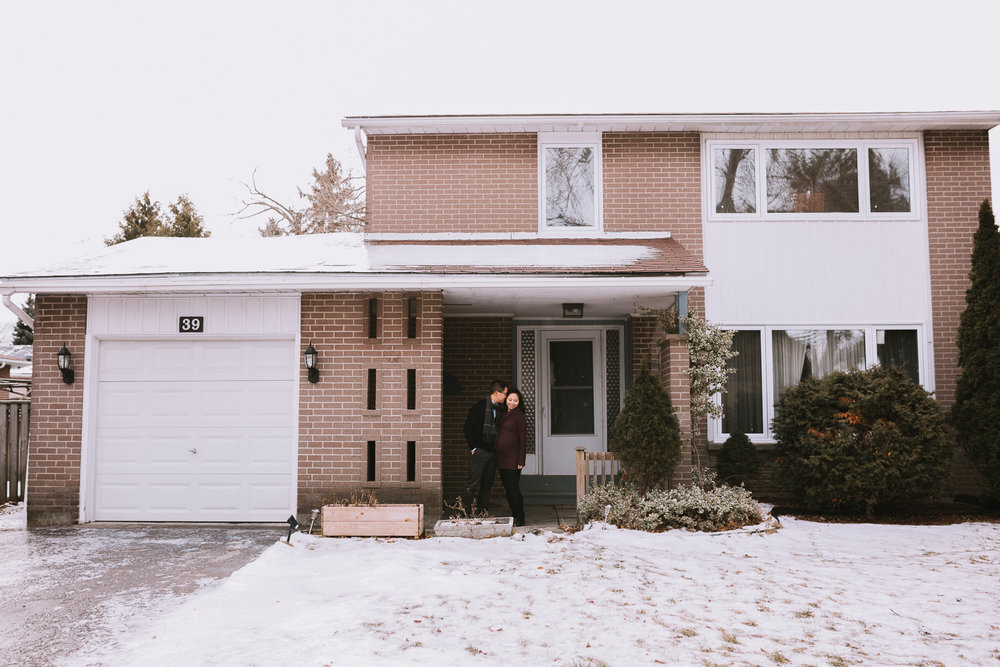 couple expecting first baby in front of first home - Newmarket lifestyle photography