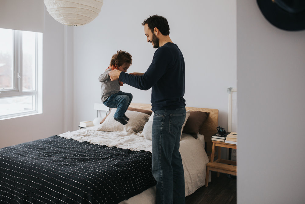 father holding 2 year old toddler son's hands as he jumps on bed - uxbridge family photography