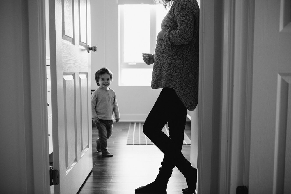 pregnant woman leans against nursery doorway, 2 year old toddler son walking by - stouffville in-home family photography